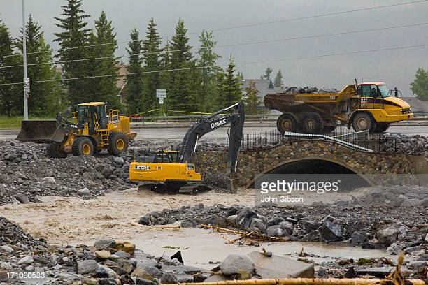 Equipment operators shore up the Elk Run Blvd bridge and clear it from debris caused by flooding of the Cougar Creek June 21 2013 in Canmore Alberta...