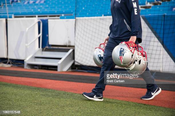 A equipment personnel member carries New England Patriots helmets to the benches before the game against the Buffalo Bills at New Era Field on...