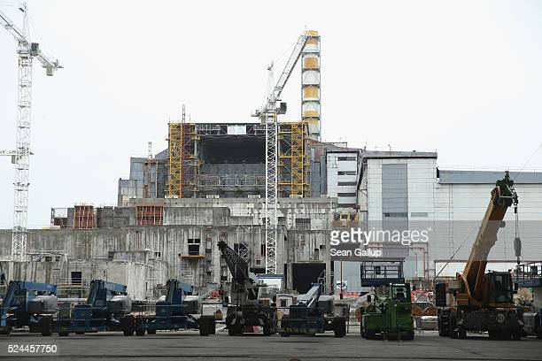 Equipment stands in front of the sarcophagus that encloses stricken reactor number four at the Chernobyl nuclear power plant on the 30th anniversary...