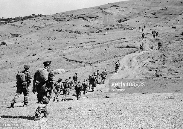 Equipmentladen paratroopers of the 5th French Foreign Legion Regiment strike out in Indian file across a rocky road here in an effort to capture the...