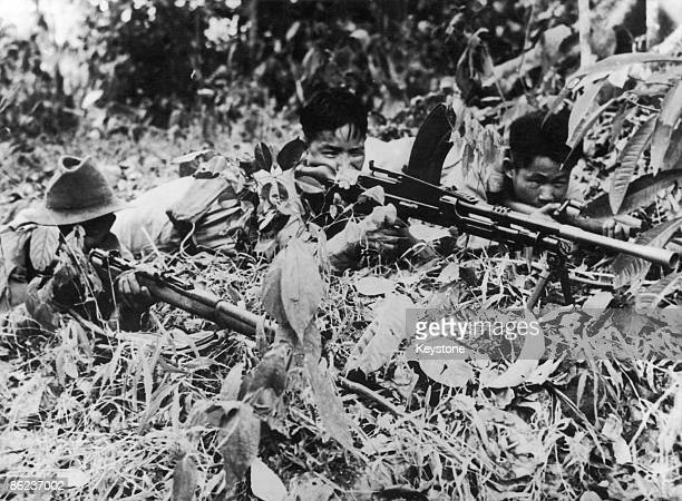 Equipped with two rifles and a machine gun Kachin tribesmen from northern Burma stalk a Japanese soldier through the jungle during World War II 1945...