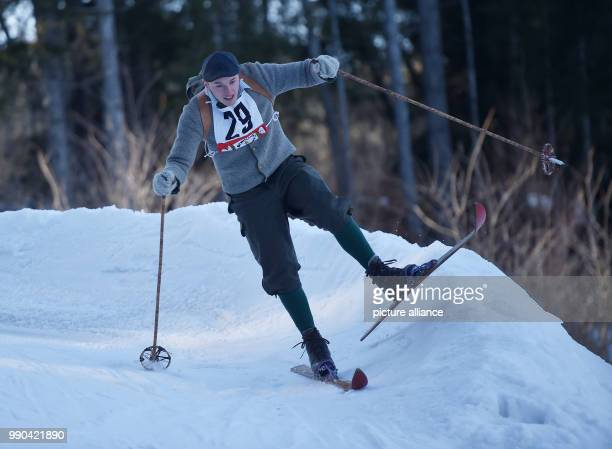 Equipped with wooden skis and wearing traditional clothing, a skier navigates the obstacle course at a nostalgic ski race in Kruen, Germany, 13...