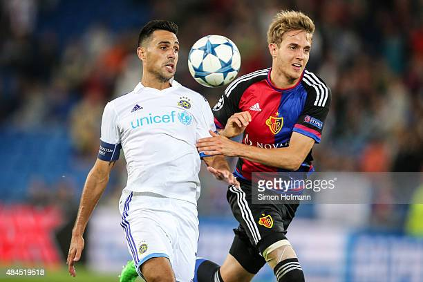 Eran Zahavi of Tel Aviv is challenged by Daniel Hoegh of Basel during the UEFA Champions League qualifying round play off first leg match between FC...