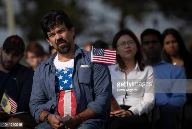 Erandy Delgobo Da Silva originally from Brazil wears an American flag shirt as he waits to take the Oath of Citizenship during a naturalization...