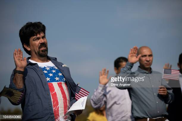 Erandy Delgobo Da Silva originally from Brazil wears an American flag shirt as he takes the Oath of Citizenship during a naturalization ceremony at...