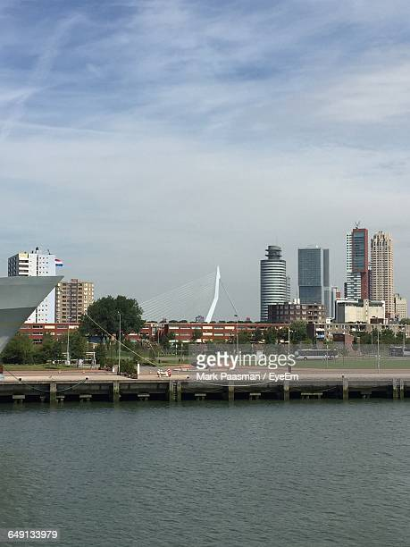 Erasmus Bridge And Buildings In Front Of River Against Cloudy Sky On Sunny Day