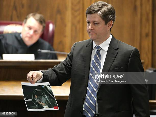 Erath County District Attorney Alan Nash carries a photo of Eddie Ray Routh handcuffed in the back of a Lancaster Police car the night of his arrest...