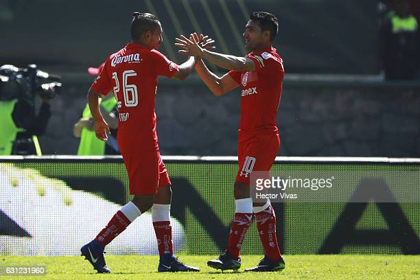 Erbin Trejo of Toluca celebrates with teammate Antonio Naelson after scoring the fourth goal of his team during the 1st round match between Toluca...