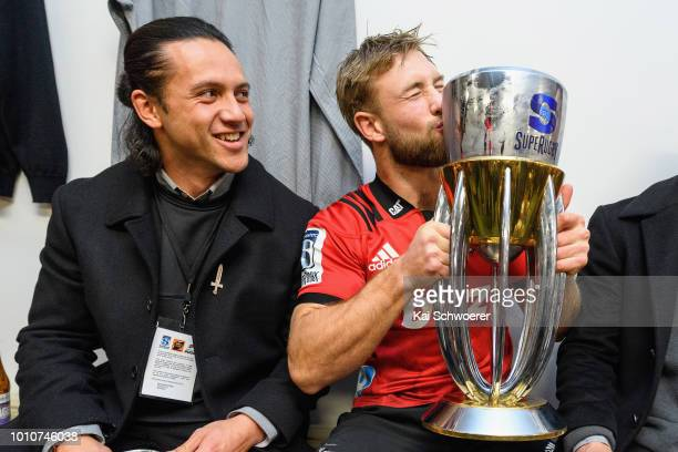 Ere Enari looks on as Braydon Ennor of the Crusaders kisses the Super Rugby Trophy in their dressing room after their win in the Super Rugby Final...