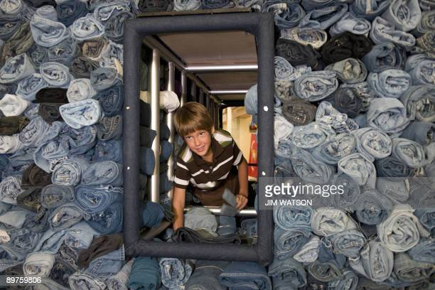 Erek Hansen a 9yearold who organized a denim drive that collected nearly 1700 pairs of jean crawls through a display at Union Station in Washington...