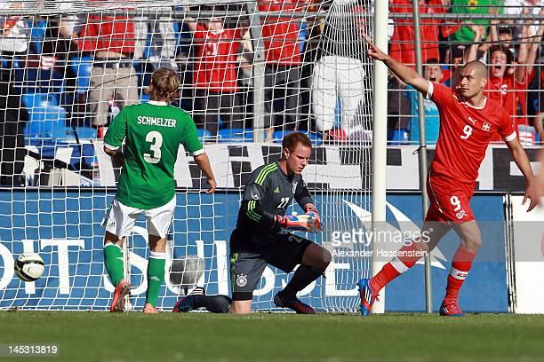 Eren Derdiyok of Switzerland scores the opening goal against MarcAndre Ter Stegen keeper of Germany and his team mate Marcel Schmelzer during the...