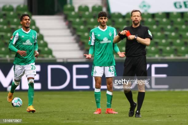 Eren Dinkci of SV Werder Bremen reacts after receiving a red card from Matthias Jollenbeck, the match referee during the Bundesliga match between SV...