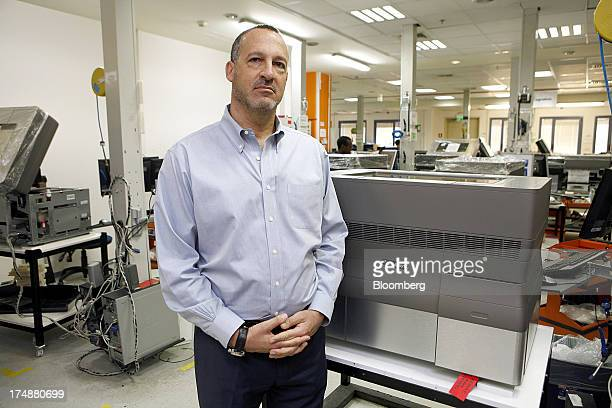 Erez Simha chief financial officer and chief operating officer of Stratasys Ltd poses for a photograph beside a 3D printing machine at the company's...