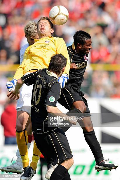 Erfurts goalkeeper Dirk Orlishausen and Regensburgs Marco Haller and Bashiru Gambo fight for the ball during the Third League match between Rot-Weiss...