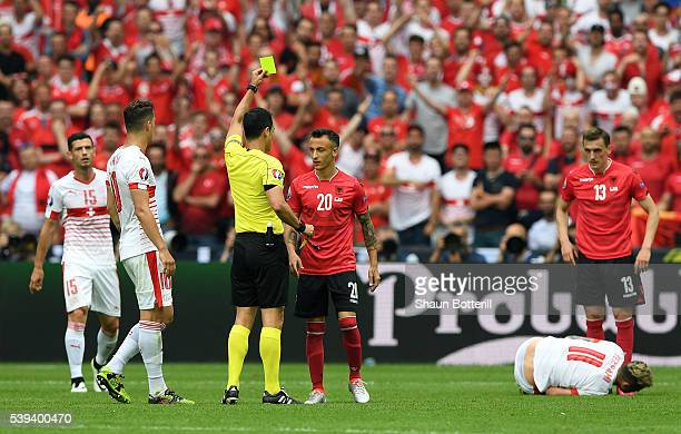 Ergys Kace of Albania is shown a yellow card by Referee Carlos Valesco Caballo during the UEFA EURO 2016 Group A match between Albania and...