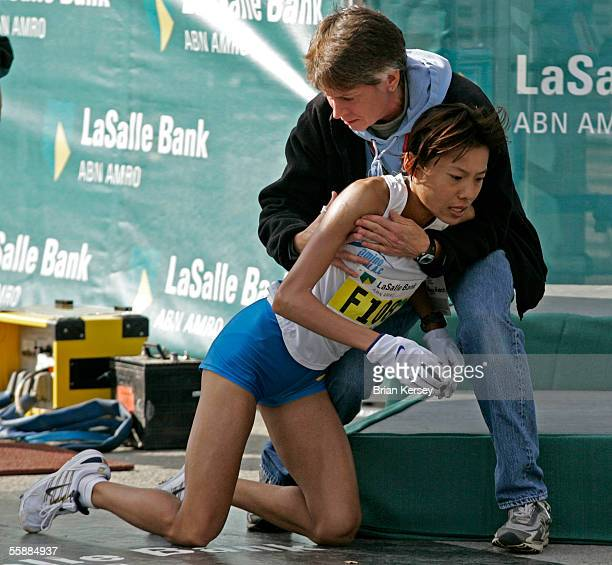 Eri Hayakawa of Japan is helped up after falling at the finish line at the 2005 LaSalle Bank Chicago Marathon October 9 2005 in Chicago Illinois...