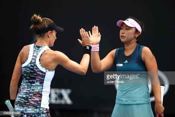 Eri Hozumi of Japan and Alicja Rosolska of Poland talk tactics in their first round doubles match against Andrea Petkovic of Germany and Monica Puig...