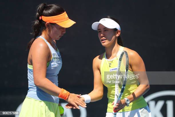 Eri Hozumi of Japan and Miyu Kato of Japan talk tactics in their first round women's doubles match against Storm Sanders of Australia and Monique...