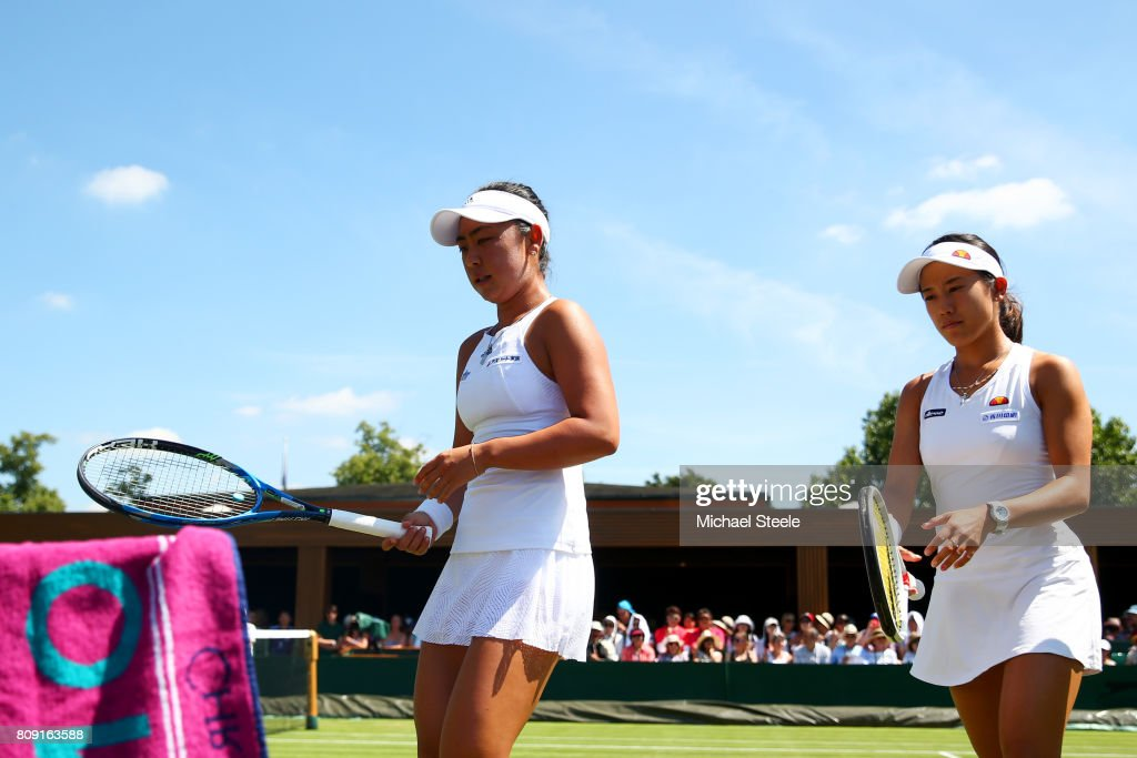 Eri Hozumi of Japan and Miyu Kato of Japan walk to their seat as there is a break in play in their during the Ladies Doubles first round match against Monique Adamczak of Australia and Storm Sanders of Australia on day three of the Wimbledon Lawn Tennis Championships at the All England Lawn Tennis and Croquet Club on July 5, 2017 in London, England.