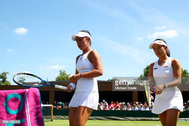 Eri Hozumi of Japan and Miyu Kato of Japan walk to their seat as there is a break in play in their during the Ladies Doubles first round match...