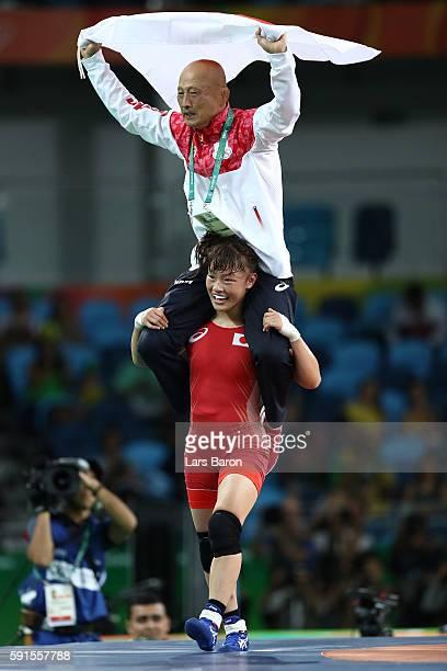 Eri Tosaka of Japan celebrates winning gold with coach Kazuhito Sakai over Mariya Stadnik of Azerbaijan in the Women's Freestyle 48kg event on Day 12...
