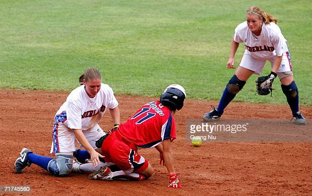 Eri Yamada of Japan is safe at second base as Lynn Geertman and Daisy De Peinder of the Netherlands play the ball during ISF XI Women's Fast Pitch...