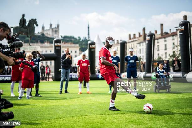 Eric Abidal kicks a ball with a mask to feel like a blind player during the EqualGame Match at the Fan Zone ahead of the UEFA Europa League Final...
