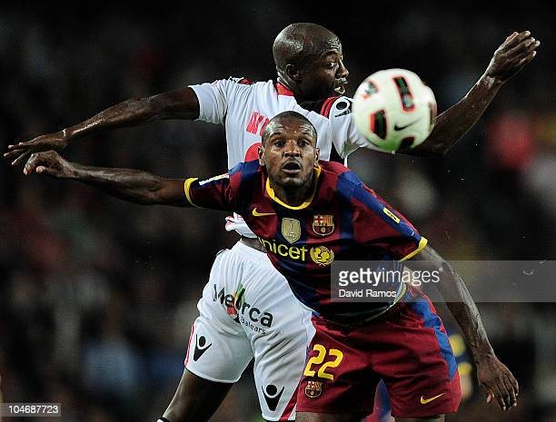 Eric Abidal of Barcelona duels for a high ball with Pierre Webo of Mallorca during the La Liga match between Barcelona and Mallorca at the Camp Nou...
