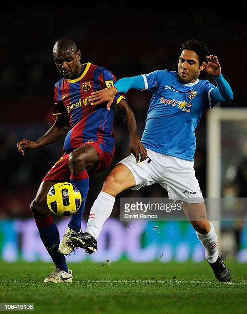 Eric Abidal of Barcelona duels for the ball against Jose Ortiz of Almeria during the Copa del Rey Semi Final First Leg match between Barcelona and...