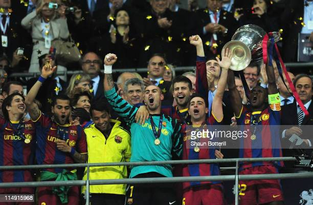 Eric Abidal of FC Barcelona lifts the trophy and celebrates with teammates after victory in the UEFA Champions League final between FC Barcelona and...