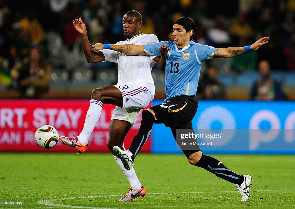 Eric Abidal of France and Sebastian Abreu of Uruguay battle for the ball during the 2010 FIFA World Cup South Africa Group A match between Uruguay and France at Green Point Stadium on June 11, 2010 in Cape Town, South Africa.