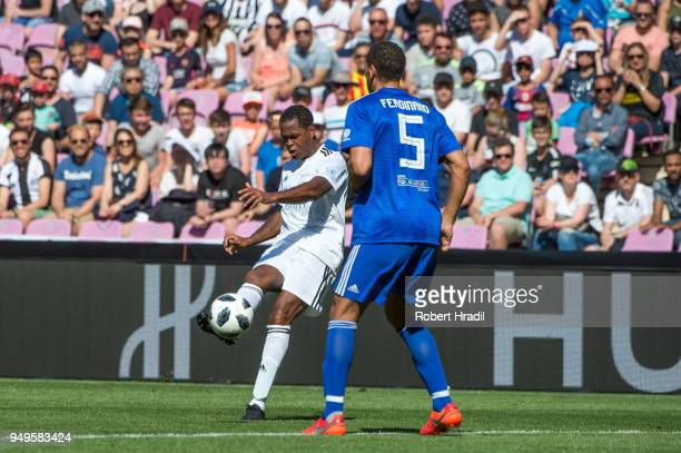 Eric Abidal passes the ball over Rio Ferdinand during the UEFA Match for Solidarity at Stade de Geneva on April 21 2018 in Geneva Switzerland