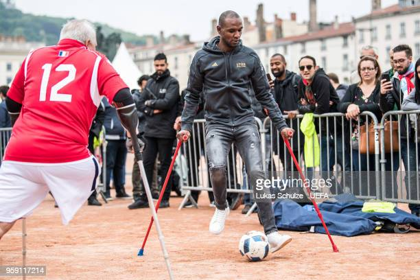 Eric Abidal plays soccer with crutches during his visit at European Amputee Football Federation at the Fan Zone ahead of the UEFA Europa League Final...