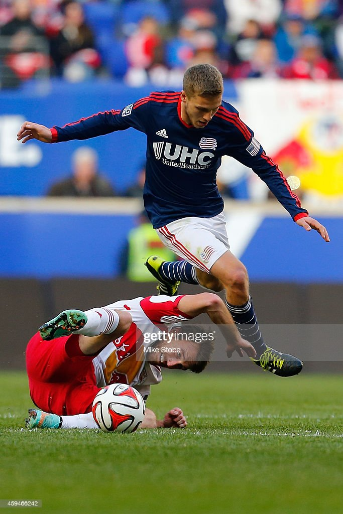Eric Alexander #12 of New York Red Bulls falls to the pitch playing the ball against Scott Caldwell #6 of New England Revolution during the Eastern Conference Final - Leg 1 at Red Bull Arena on November 23, 2014 in Harrison, New Jersey.