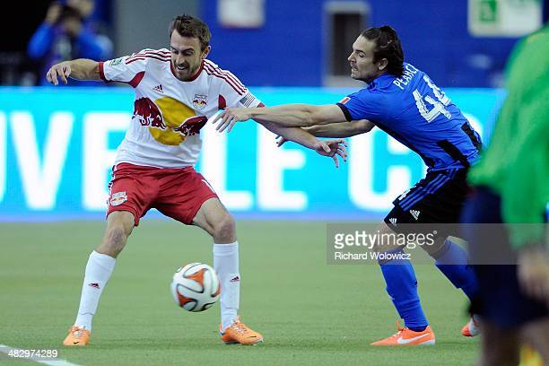 Eric Alexander of the New York RedBulls and Heath Pearce of the Montreal Impact battle for the ball during the MLS game at the Olympic Stadium on...