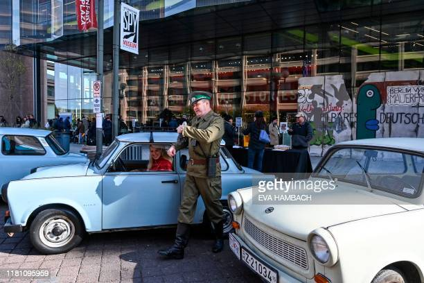 Eric Allen from Indiana in full East German officer garb poses for a visitor with his vintage Trabant car regarded as a symbol of East Germany and...