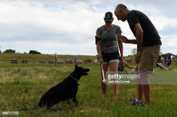 Eric Amtsberg gives his dog Lola a command as Nichole Amtsberg prepares to throw a tennis ball at USMC CPL David M Sonka Dog Park on June 14 in...