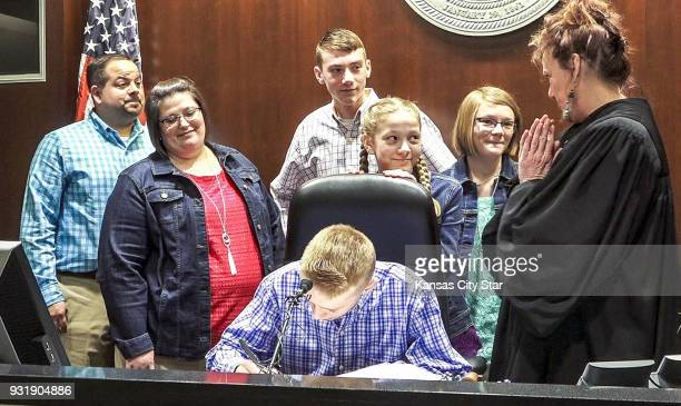 Eric and Phyllis Watson of Gardner watch as newly adopted son Cody signs documents during an adoption hearing on Monday March 12 2018 in Olathe in...