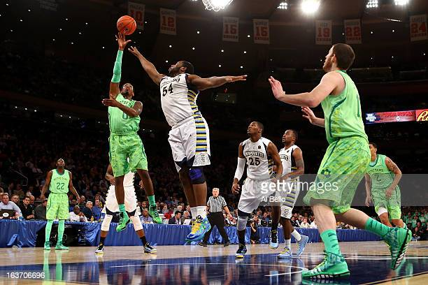 Eric Atkins of the Notre Dame Fighting Irish drives for a shot attempt against Davante Gardner of the Marquette Golden Eagles during the quaterfinals...