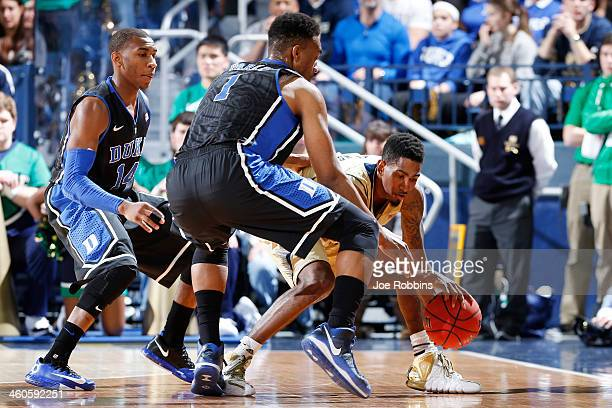 Eric Atkins of the Notre Dame Fighting Irish goes for a loose ball against Jabari Parker and Rasheed Sulaimon of the Duke Blue Devils during the game...