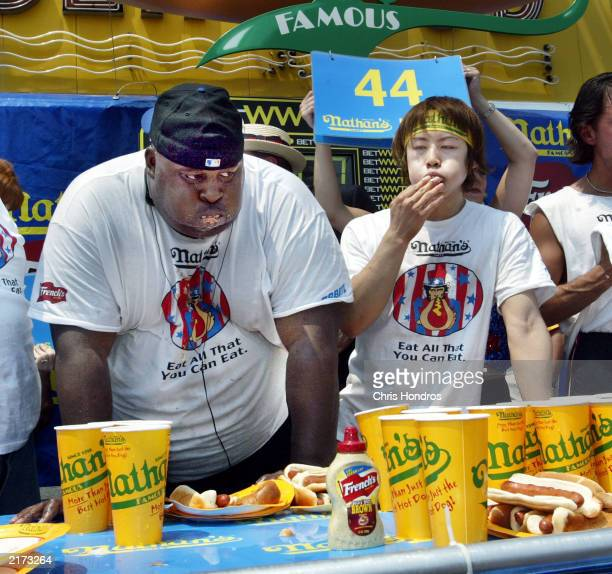 Eric 'Badlands' Booker of New York and Takeru Kobayashi of Japan stuff hot dogs in their mouths at the end of the annual hot dog eating contest at...