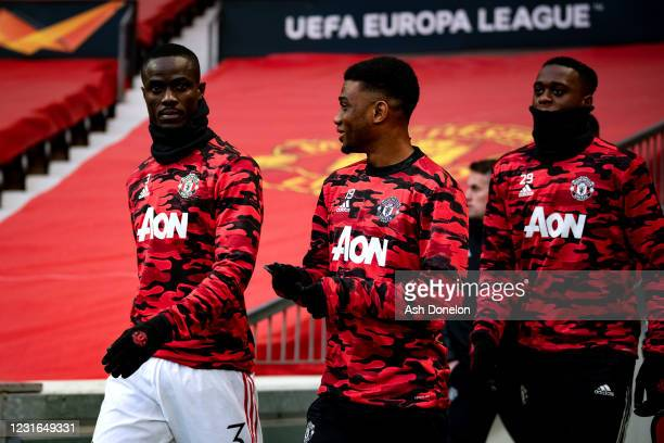 Eric Bailly, Amad and Aaron Wan-Bissaka of Manchester United walk out to warm up prior to the UEFA Europa League Round of 16 First Leg match between...
