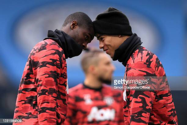 Eric Bailly of Manchester United goes head-to-head with Mason Greenwood of Manchester United before the Premier League match between Manchester City...