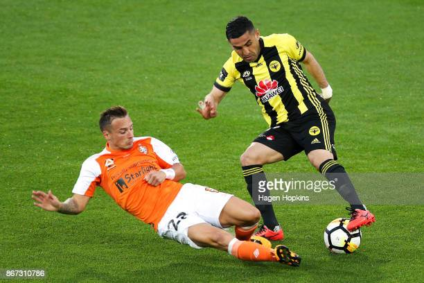 Eric Bautheac of Brisbane tackles Ali Abbas of the Phoenix during the round four ALeague match between the Wellington Phoenix and the Brisbane Roar...