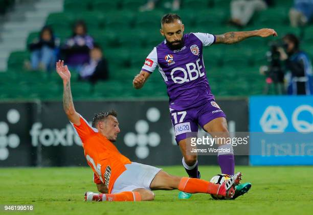 Eric Bautheac of the Brisbane Roar makes a sliding tackle against Diego Castro of the Perth Glory during the round 27 ALeague match between the Perth...