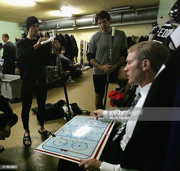 Eric Belanger and Brendan Shanahan take pregame instructions from assistant coach Marty McSorley prior to the Primus Worldstars game against SC Bern...