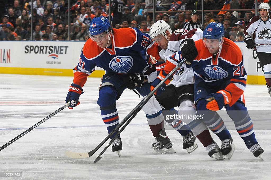 Eric Belanger #20 and Magnus Paajarvi #91 of the Edmonton Oilers battle for the puck against Chuck Kobasew #12 of the the Colorado Avalanche at Rexall Place on January 28, 2013 in Edmonton, Alberta, Canada.