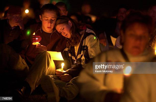 Eric Benson from Chatfield High and Jillian Draper from Dakota Ridge High listen to comments from clergy April 20 2000 during a candlelight vigil in...