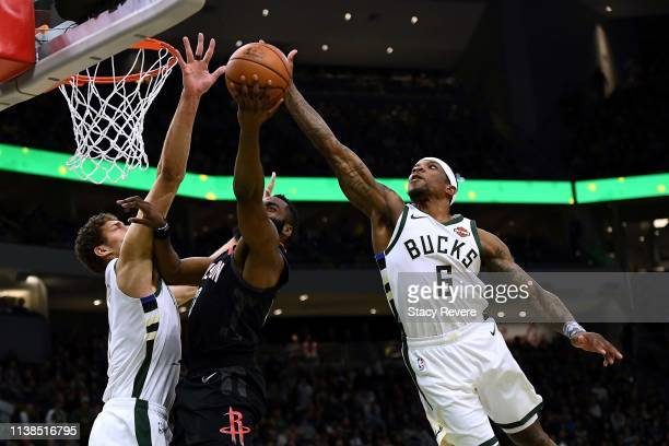 Eric Bledsoe of the Milwaukee Bucks blocks a shot by James Harden of the Houston Rockets during the second half of a game at Fiserv Forum on March 26...
