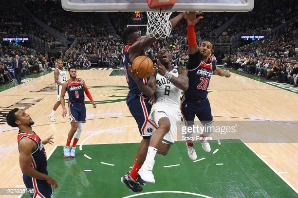 Eric Bledsoe of the Milwaukee Bucks drives to the basket against Thomas Bryant and Gary Payton II of the Washington Wizards during the second half at...